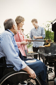 Grandparents with brothers barbecuing at yard - MASF04390