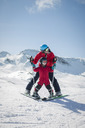 Full length of man teaching son to ski on snowy mountain - MASF04396