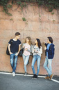 Full length of teenagers talking while leaning on wall - MASF04405