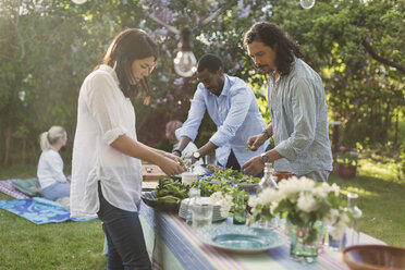 Friends preparing food at dining table in backyard during summer party - MASF04414