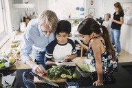 Grandfather and children preparing food in kitchen - MASF04423