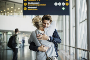 Happy businessman embracing colleague at airport - MASF04426