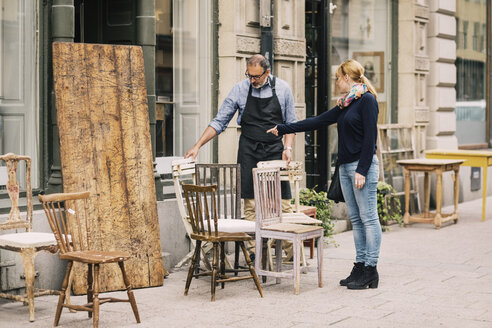 Female costumer pointing while retailer looking at chair outside antique shop - MASF04432