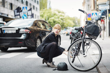 Businesswoman looking away while repairing bicycle on street - MASF04438