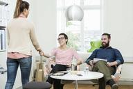 Businesswomen shaking hands in creative office - MASF04441
