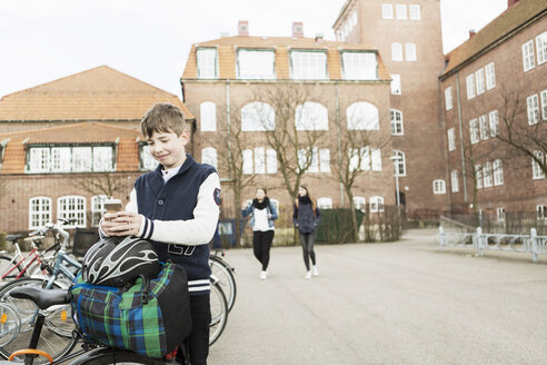 Boy using mobile phone at bicycle parking area outside school building - MASF04468