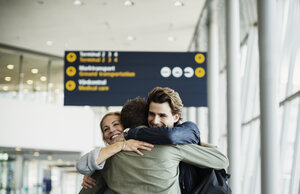Affectionate business colleagues embracing at airport - MASF04474