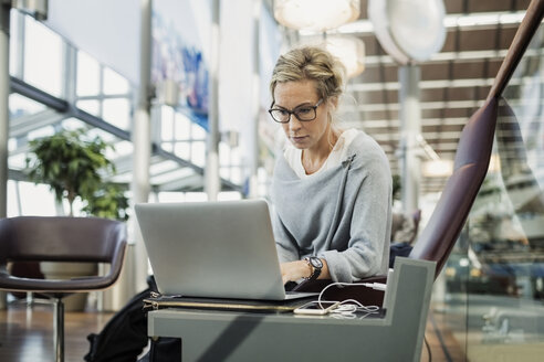 Businesswoman using laptop at airport lobby - MASF04477