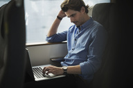 Businessman using laptop while traveling in train - MASF04480