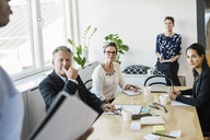 Business people looking at male colleague during meeting in office - MASF04489