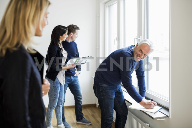 Smiling mature real estate agent looking at colleague white couple looking through window at home - MASF04507