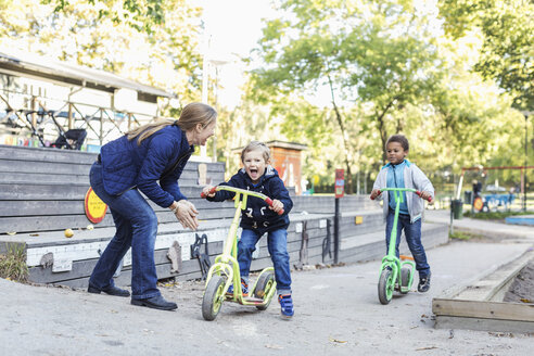 Teacher motivating children on push scooters during race - MASF04528