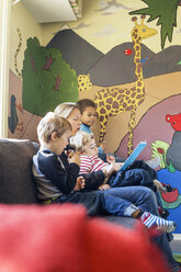 Teacher telling story to children in kindergarten - MASF04531