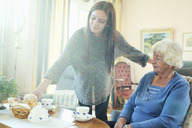 Young woman serving breakfast to grandmother at home - MASF04585