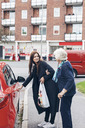 Young woman opening car door for grandmother on city street - MASF04588