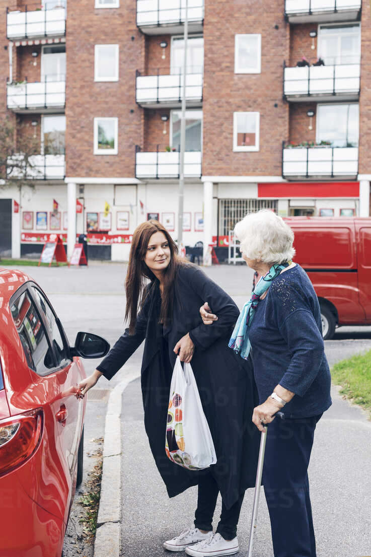 Young woman opening car door for grandmother on city street - MASF04588 - Maskot ./Westend61