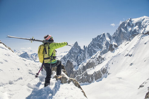 Side view of hiker with skis standing on snow covered mountain against clear blue sky - CAVF38562