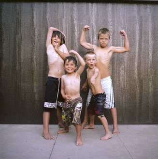 Portrait of boys flexing muscles while standing against wall - CAVF38622