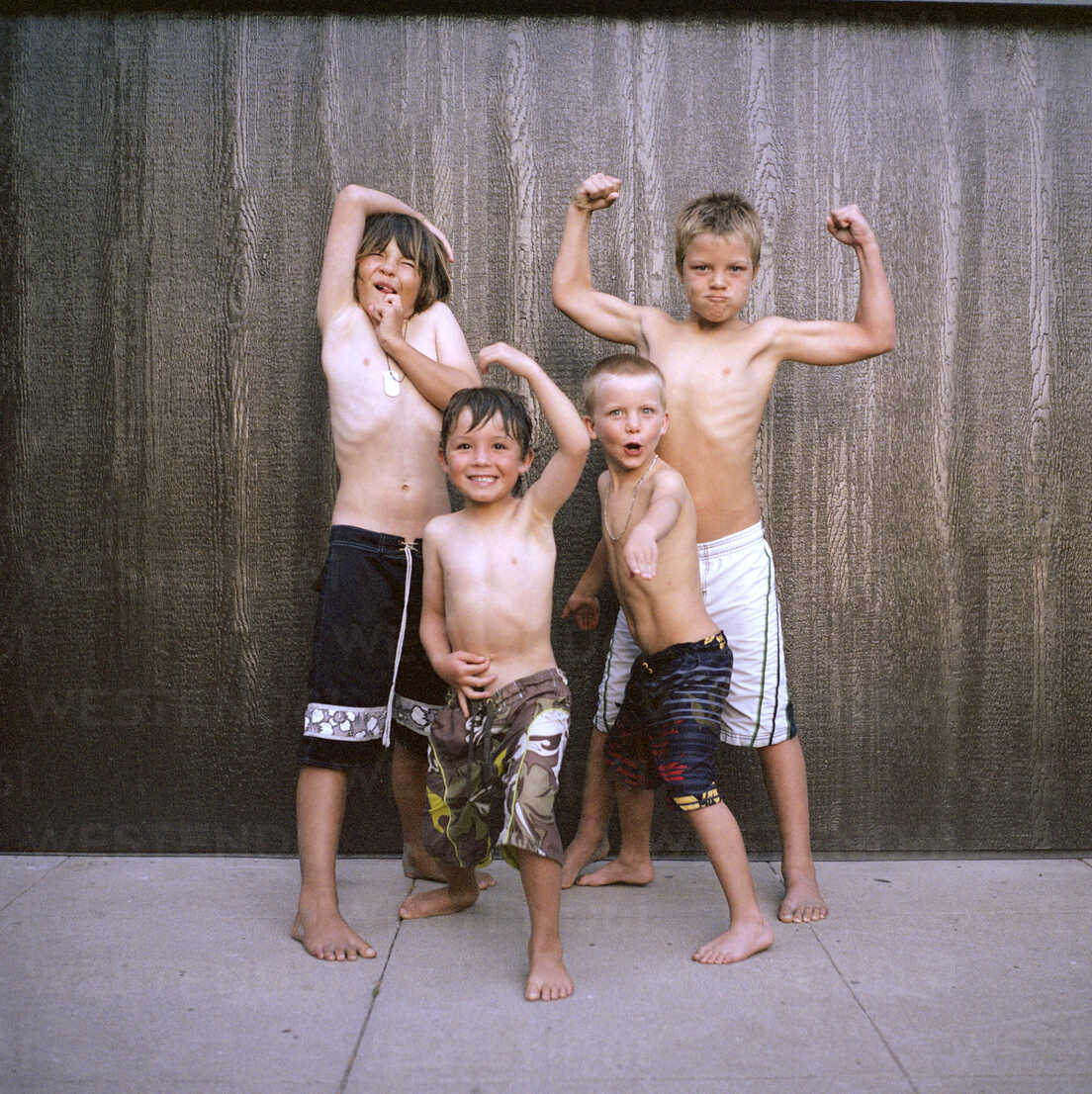 Portrait of boys flexing muscles while standing against wall - CAVF38622 - Cavan Images/Westend61