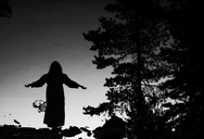 Reflection of silhouette woman with arms outstretched in lake - MASF04624