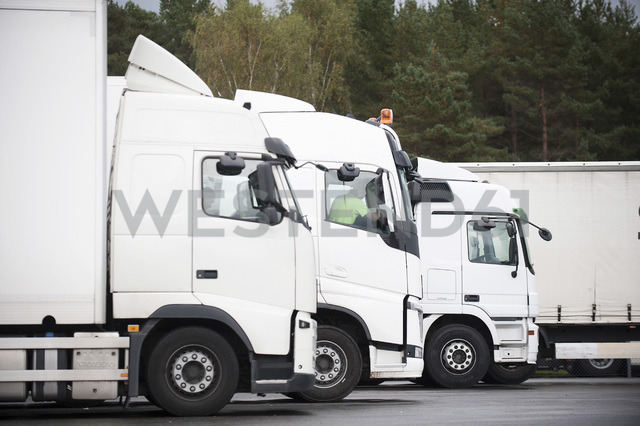 Row of commercial trucks parked on road - MASF04627