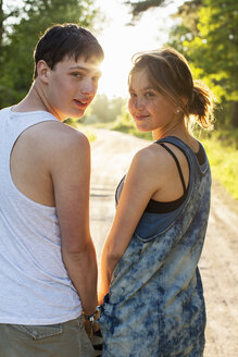 Rear view portrait of couple standing on dirt road - MASF04633