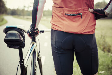 Rear view midsection of cyclist standing by bicycle on country road - MASF04639