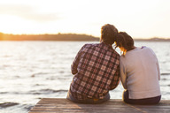 Rear view of loving couple sitting on pier against sea at sunset - MASF04648
