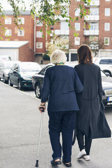 Rear view of elderly woman walking with granddaughter on sidewalk in city - MASF04657