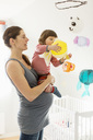 Pregnant woman carrying girl playing with toy in baby room - MASF04672