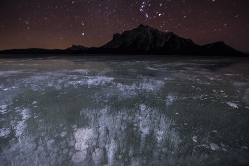 Majestic view of methane bubbles in Abraham Lake by mountains during night - CAVF38628