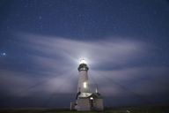 Low angle scenic view of Yaquina Head Lighthouse on shore against star field - CAVF38697