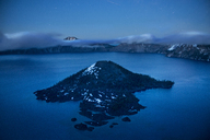 High angle view of Wizard Island amidst Crater Lake against sky during dawn - CAVF38751