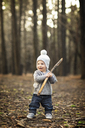 Playful baby boy holding stick while standing on field - CAVF38793
