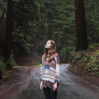 Young woman looking up while standing on road in forest - CAVF38850