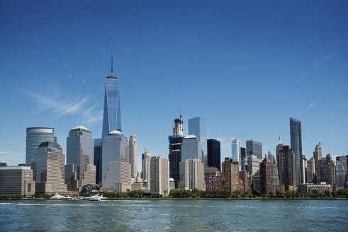 Modern NYC skyline by sea against sky - CAVF38886
