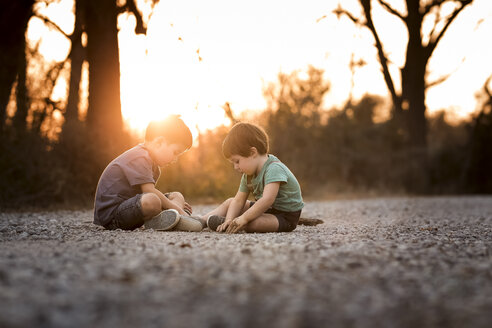 Brothers playing with dirt on road against sky during sunset - CAVF38898