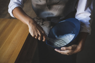 Midsection of woman whisking batter in bowl while standing by table - CAVF38955