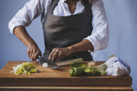 Midsection of woman cutting scallions in kitchen against wall - CAVF38961