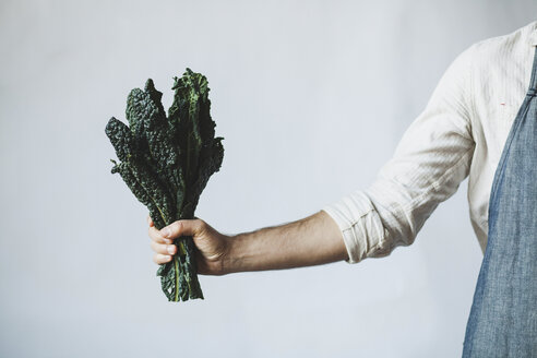 Midsection of man holding kale while standing against white wall at home - CAVF38964