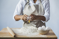 Midsection of woman breaking egg in flour on table while standing against wall at home - CAVF38967