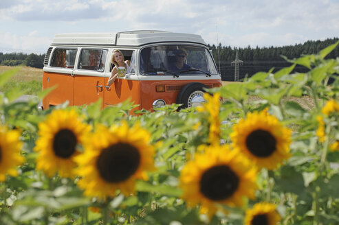 Couple in old camper driving through sunflower field - CRF02782