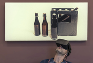 Man wearing VR glasses under photography of beer crate - PAF01817