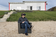 Man sitting in armchair on the beach wearing VR glasses - PAF01826