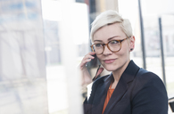 Portrait of confident businesswoman on cell phone in office - UUF13332