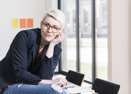 Portrait of confident businesswoman sitting on table in office - UUF13335
