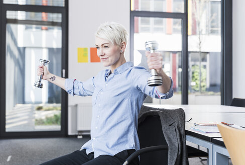 Smiling woman exercising with dumbbells in office - UUF13362