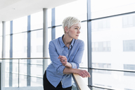 Woman in office building leaning on railing - UUF13365