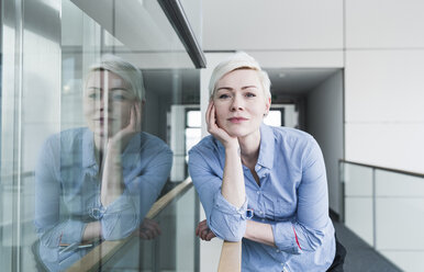 Portrait of woman on office floor leaning on railing - UUF13368