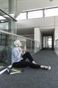 Woman sitting on office floor enjoying listening to music with headphones - UUF13371